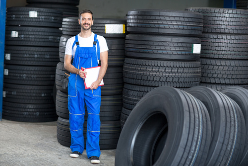 smiling mechanic checing clipboard car tires