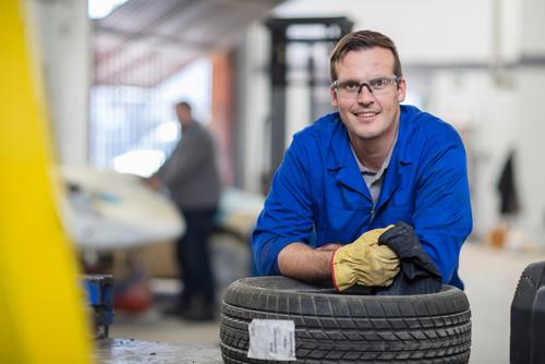 Portrait of male car mechanic leaning against tyres in repair ga